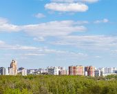 image of cloud forest  - blue sky with white clouds over city and green forest in sunny spring day - JPG