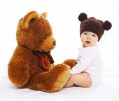 stock photo of baby bear  - Portrait of cute baby in knitted brown hat with big teddy bear - JPG