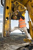 stock photo of foundation  - Construction worker climbing on drilling pile foundation - JPG