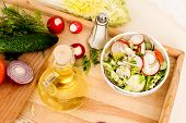 foto of chinese parsley  - Spring salad with radishes cucumber Chinese cabbage and red onion closeup vsteklyannoy bowl on a white wooden background - JPG