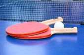 picture of ping pong  - Two table tennis or ping pong rackets and ball on blue table with net - JPG