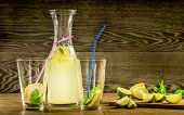 foto of refreshing  - Refreshing lemonade drink and ripe fruits against wooden background - JPG