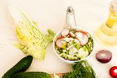 foto of chinese parsley  - Spring salad with radishes cucumber Chinese cabbage and red onion closeup in glass bowl on a white wooden background - JPG