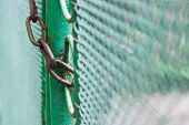 picture of chain link fence  - Close up chain locked on green color fence gate - JPG