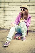 picture of snickers  - Beautiful teenage girl in cap and sunglasses sits on a skateboard near urban brick wall vertical photo with warm retro tonal correction effect instagram old style filter - JPG