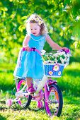 stock photo of little young child children girl toddler  - Happy child riding a bike - JPG