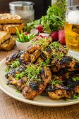 foto of chive  - Grilled teriyaki chicken wings with chive and microgreens on top garlic toast with fresh herbs and czech beer - JPG