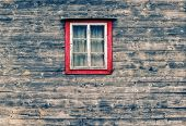 stock photo of wooden shack  - Wooden facade of a mountain hut with an old window and curtains in the center of the picture - JPG