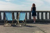 pic of balustrade  - A young woman is standing by a wall with concrete balustrades on a promenade and is admiring the sea there are two deck chairs next to her - JPG