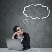 picture of daydreaming  - Young female entrepreneur working with laptop while daydreaming and looking at cloud tag - JPG
