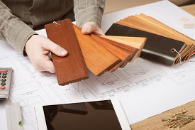 image of up-skirt  - Professional interior designer holding wood swatches for baseboard and skirting hands close up with desktop on background - JPG