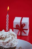 picture of birthday-cake  - birthday cupcake with a single candle on it on red background - JPG