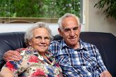 image of elderly couple  - an elderly couple sitting on a couch in their house - JPG