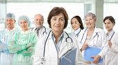 picture of medical staff  - Team of medical professionals lead by senior female doctor looking at camera - JPG