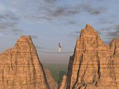 picture of aerialist  - woman walking on a tight rope between two high peaks - JPG
