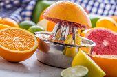 Preparation Of Orange Grape Or Multivitamin Juice, Hands Squeeze Juice On A Manual Metal Juicer Surr poster