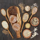 High fiber health food concept with fresh whole grain bread rolls, cereals and grains. Rustic backgr poster