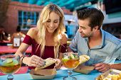 romantic couple eating street tacos at outdoor mexican restaurant poster