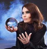 stock photo of witch ball  - Young beautiful woman with crystal ball - JPG