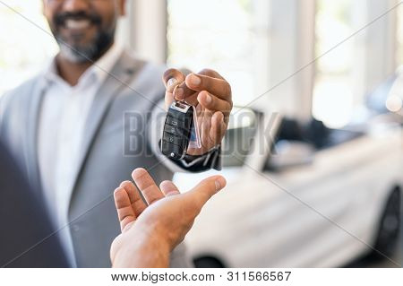 poster of Closeup hand of cardealer giving new car key to customer. Salesman hand giving keys to a client at s