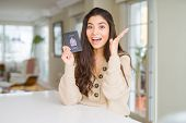 Young woman holding passport of Canada very happy and excited, winner expression celebrating victory poster