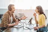 Two Radio Hosts In Headphones Talking While Recording Podcast In Radio Studio poster