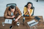 Overhead View Of Two Cheerful Radio Hosts Recording Podcast While Sitting At Wooden Table poster