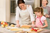 stock photo of mother child  - Mother and daughter making apple pie together grandmother check recipe - JPG
