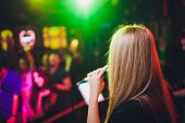 Beauty Model Girl Singer With A Microphone Singing And Dancing Over Holiday Glowing Background. Kara poster