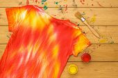 Yellow And Red Paint And A Tie Dye T-shirt On A Wooden Table. Staining Fabric In Tie Dye Style. Flat poster
