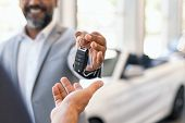 Closeup hand of cardealer giving new car key to customer. Salesman hand giving keys to a client at s poster