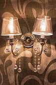 picture of scrollwork  - Vintage wall lamp hanging on scrollwork wall - JPG