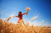 Happy woman enjoying the life in the field Nature beauty, blue sky and field with golden wheat. Outd poster