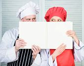 Man And Woman Chef Hide Faces Behind Open Book. Guy And Girl Read Book Recipes. Culinary Concept. Fa poster