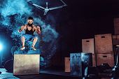 Fit Tattoed Bearded Man Jumping Onto A Box As Part Of Exercise Routine. Man Doing Box Jump In The Gy poster