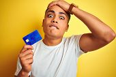 Young brazilian customer man holding credit card standing over isolated yellow background stressed w poster