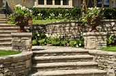 stock photo of wall-stone  - Natural stone landscaping in front of a house - JPG