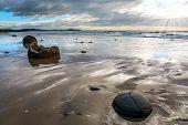 Moerakis huge round boulders on a sandy beach. The Pacific ocean tide begins. New Zealand. The sun poster