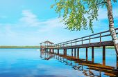 Pier On The Lake With Calm Water Under A Bright Blue Sky. Soothing Calm Minimalistic Landscape. Tree poster