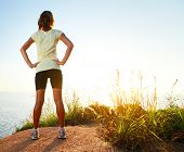 Young slim lady worn training clothes standing on countryside path and enjoying sunset