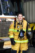 foto of breather  - Attractive female firefighter stands in front of fire truck - JPG