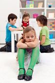 image of shy girl  - Sad little girl sitting excluded by the other kids - JPG
