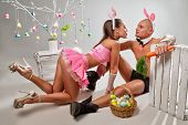 stock photo of bunny costume  - Lovely couple in rabbit costumes with carrots and eggs - JPG