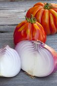 image of boeuf  - Coeur de Boeuf Tomatoes and large red Onions from Weekly Market in South France on a old wooden Table - JPG