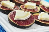 closeup of a plate with sliced figs with cheese, served as appetizer