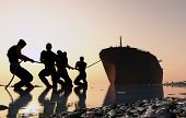 image of barge  - Group of people pulling a tanker - JPG