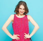 stock photo of blouse  - beautiful girl in a red blouse with polka dots on a blue background - JPG