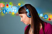 Pretty young woman with headphones listening to music, bubbles concept