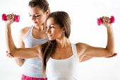 foto of shoulder muscle  - Young beautiful woman practicing upper body muscle group with personal trainer - JPG