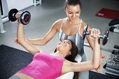 picture of work bench  - Cute Sporty young woman doing exercise in a fitness center with her personal coach - JPG